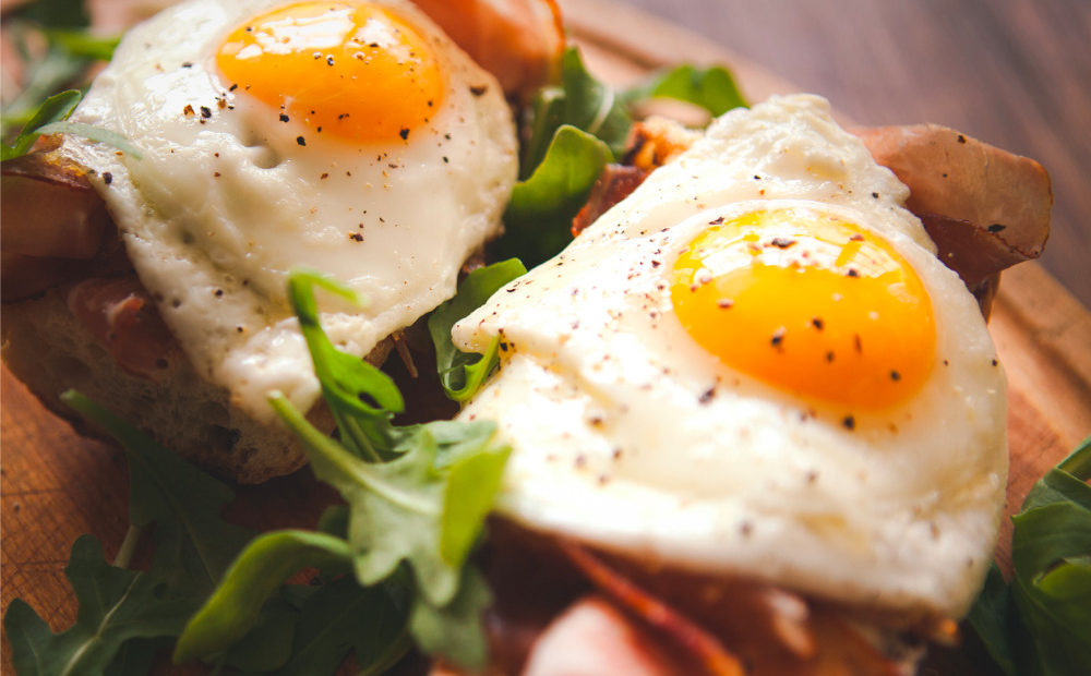 fried-eggs-sunny-side-up-on-baguette-ham-and-arugula