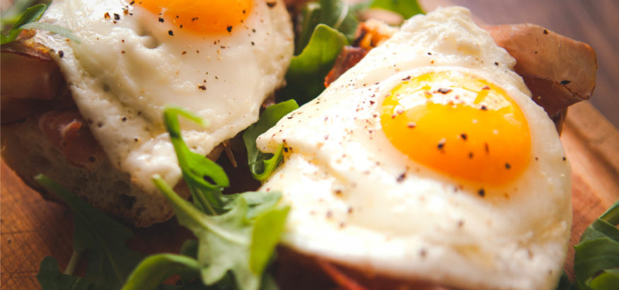 fried-eggs-sunny-side-up-on-baguette-ham-and-arugula